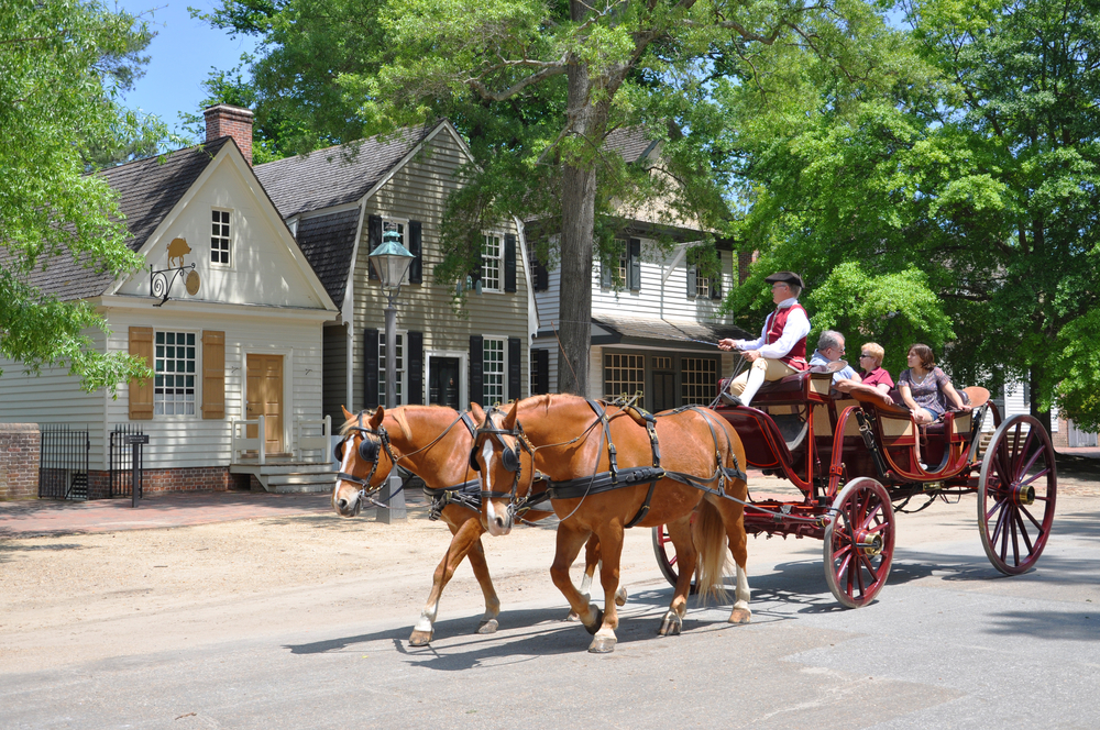 Horse drawn carriage with people riding in it passing by a house in Williamsburg.