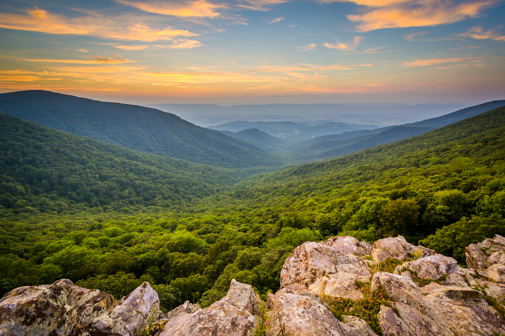The view looking down into a valley at Shenandoah National Park. The mountains are covered in trees and you can see some boulders right on the edge of the mountain. The sun is setting so the sky is yellow, orange, and blue.