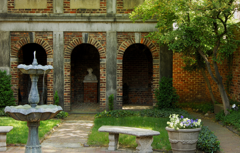 The courtyard in the Poe Museum in Richmond. There is a walkway with a fountain, a bench, and a pot of purple and white flowers. There is grass, shrubs, and a brick enclave that has a bust of Edgar Alan Poe.