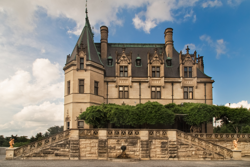The side exterior of the Biltmore Estate. It is a French Chateau style mansion with a stone terrace on the side. You can see a pergola made out of vines.
