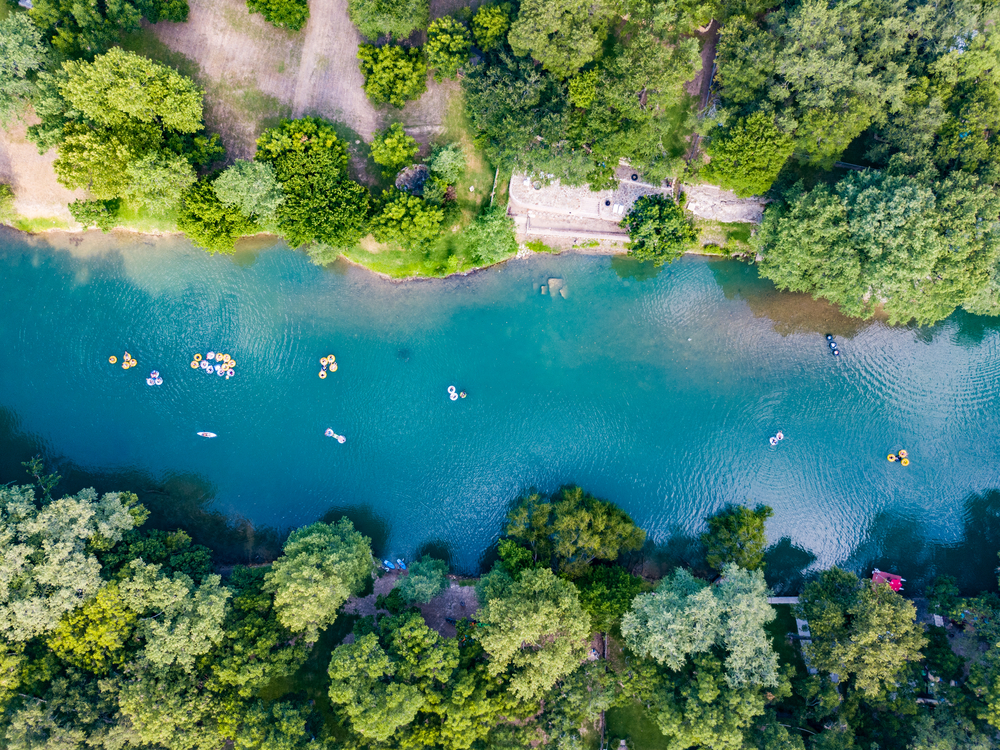 An aerial shot of people tubing on the Guadalupe River,  one of the most fun things to do in Canyon Lake, TX.