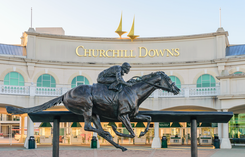 horse and jockey statue in front of churchill downs building in lousiville