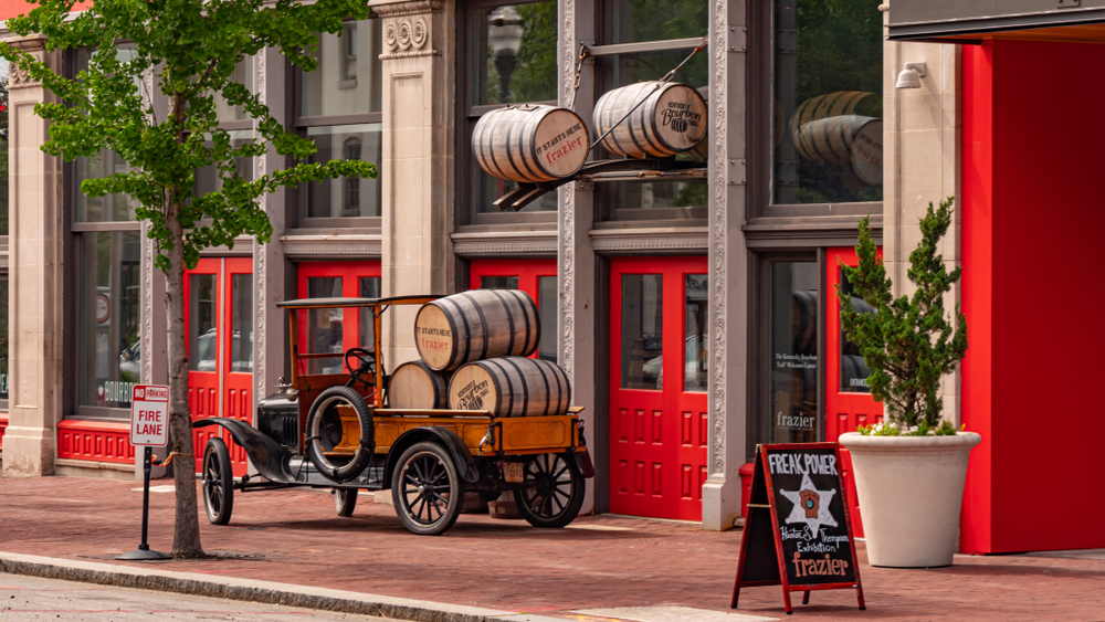 storefront with red doors and wooden barrels out front
