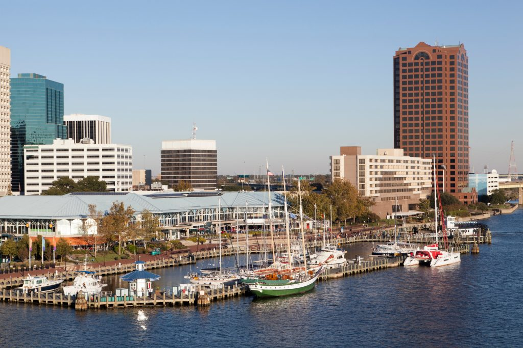 The boats line a dock in downtown Norfolk