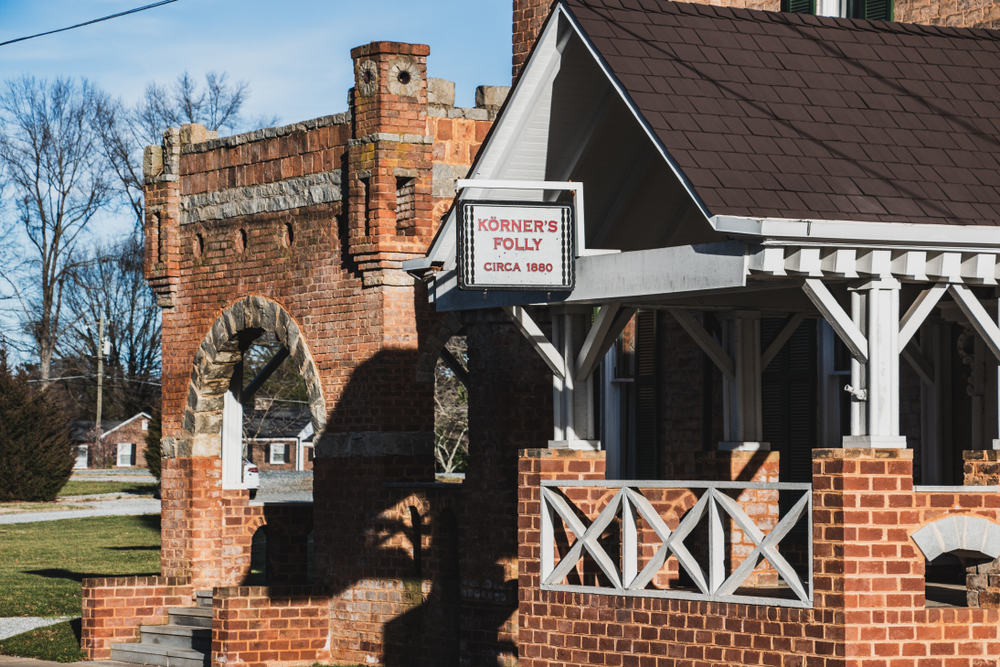 the front of korners folly, brick building with wood and stone design work