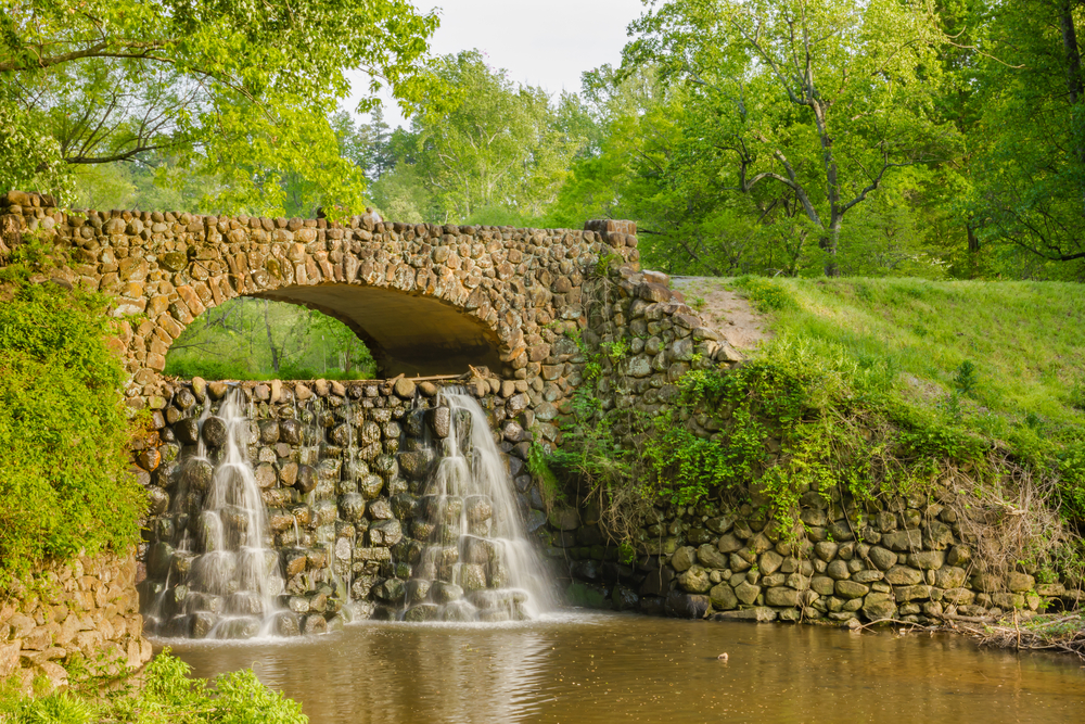 waterfall falling over mad made stone feature, surrounded by green trees and grass