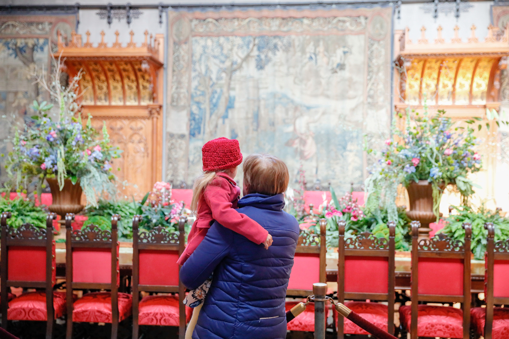 A person holding a young child as they look at the elaborate dining table in the massive dining room in the Biltmore. There are spring flowers and there are elaborate tapestries on the back wall.