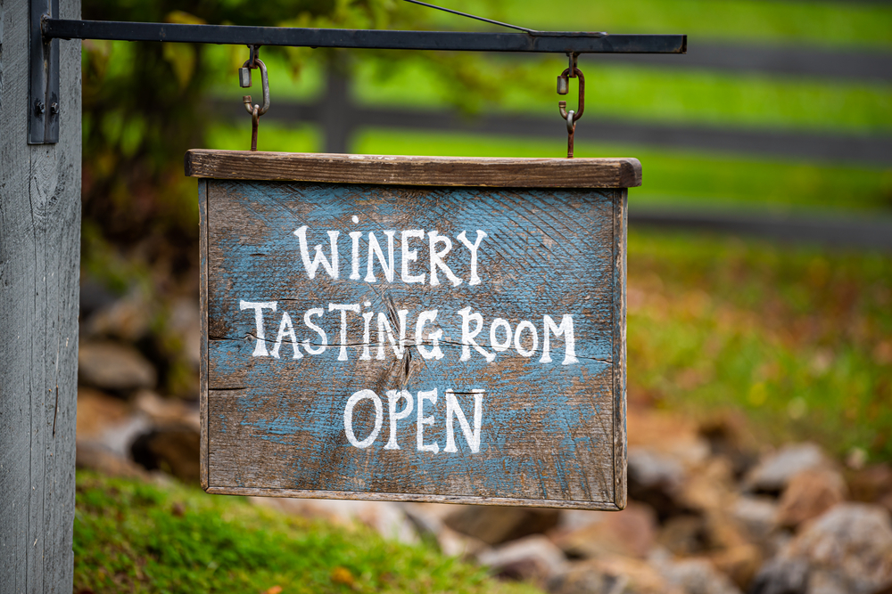 A wooden sign with faded blue paint. It says 'Winery Tasting Room Open'. It is hanging from a black metal bar. Behind it you can see a green lawn and a fence behind it.