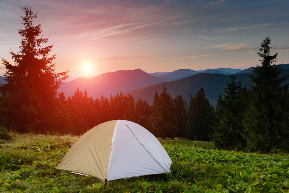 White tent overlooking trees and the Smoky Mountains at sunset