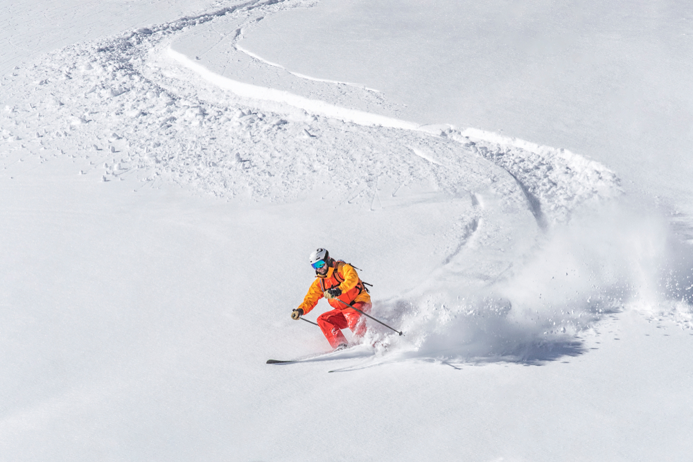 A skier headed down a snowy slope.