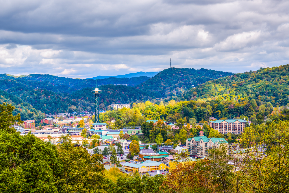 Panoramic view of Gatlinburg surrounded by trees and mountains.