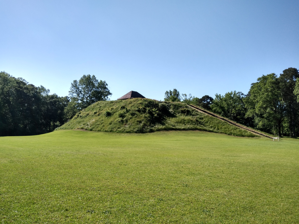 An earthen mound, with stairs leading to the top, at Explore The Moundville Archaeological Park, one of the best places to visit in Tuscaloosa, AL.