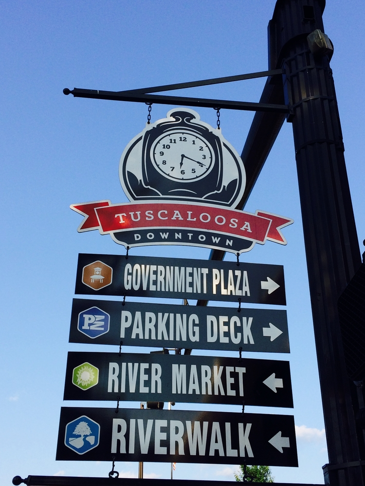 A town sign in Tuscaloosa, showing directions to the river market and river walk which are some of the best things to do in Tuscaloosa.
