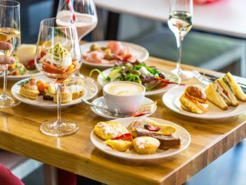 A fancy spread of brunch foods on a light wood table. You can see finger sandwiches, crepes, a salad, quiche, and a large wine glass with some sort of dessert with whipped cream in it. There are also two glasses with champagne. One of the delicious restaurants in Tupelo.