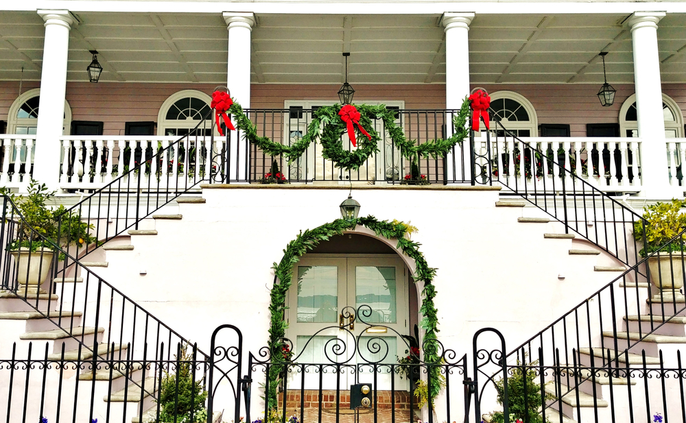 The front of a large white home with two large staircases on either side leading to a large front porch. There is greenery, a wreath, and red ribbons decorating the stair railing and door archways.