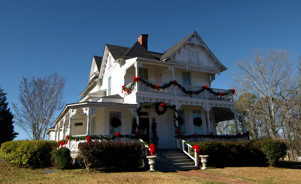 A large white historic Victorian farm house. It is decorated for Christmas with greenery on the railings of the porch, red ribbon, and wreathes.