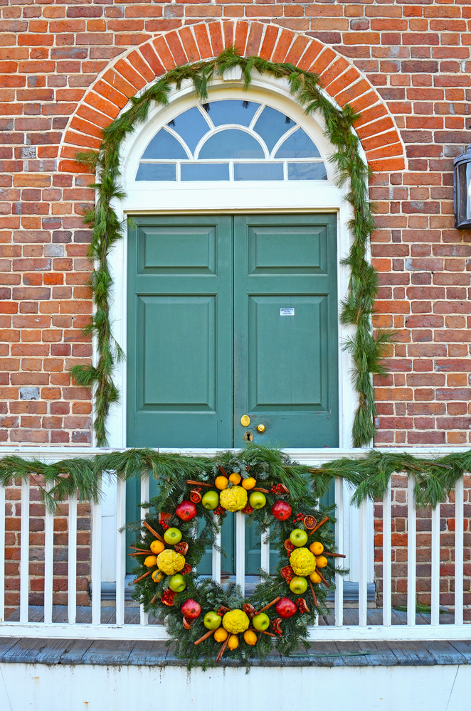 A front door in the historic Colonial Williamsburg. The door is green and the building is brick. Around the door is fresh greenery. On the railing of the porch there is more greenery and a large wreath with fresh fruits.