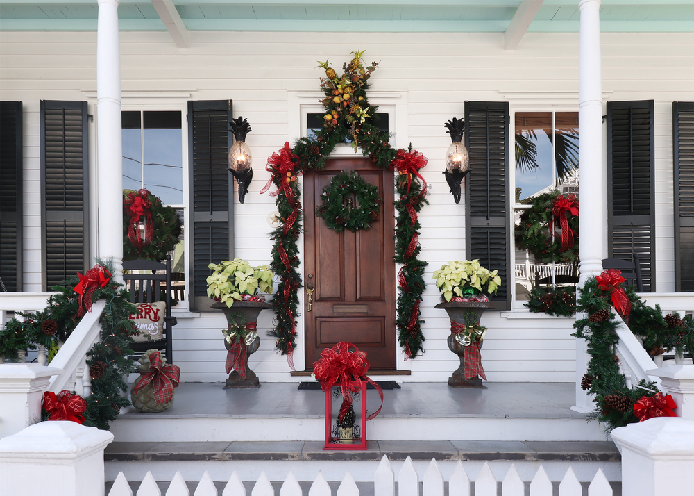 The front porch of a large white home that is elaborately decorated for Christmas with greenery, red ribbon, poinsettias, and other simple holiday decorations.