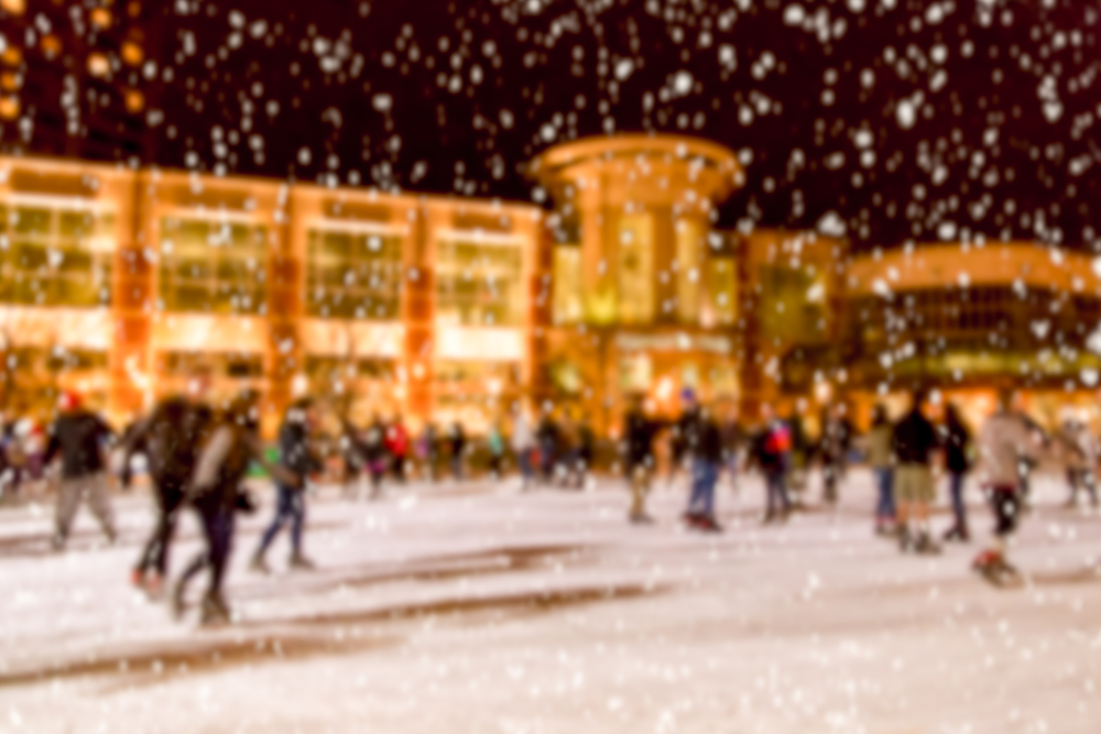 A bokeh image of people ice skating next to a large building. You can see snowflakes falling, the building appears to be orange in color, and there are lots of people on the ice.