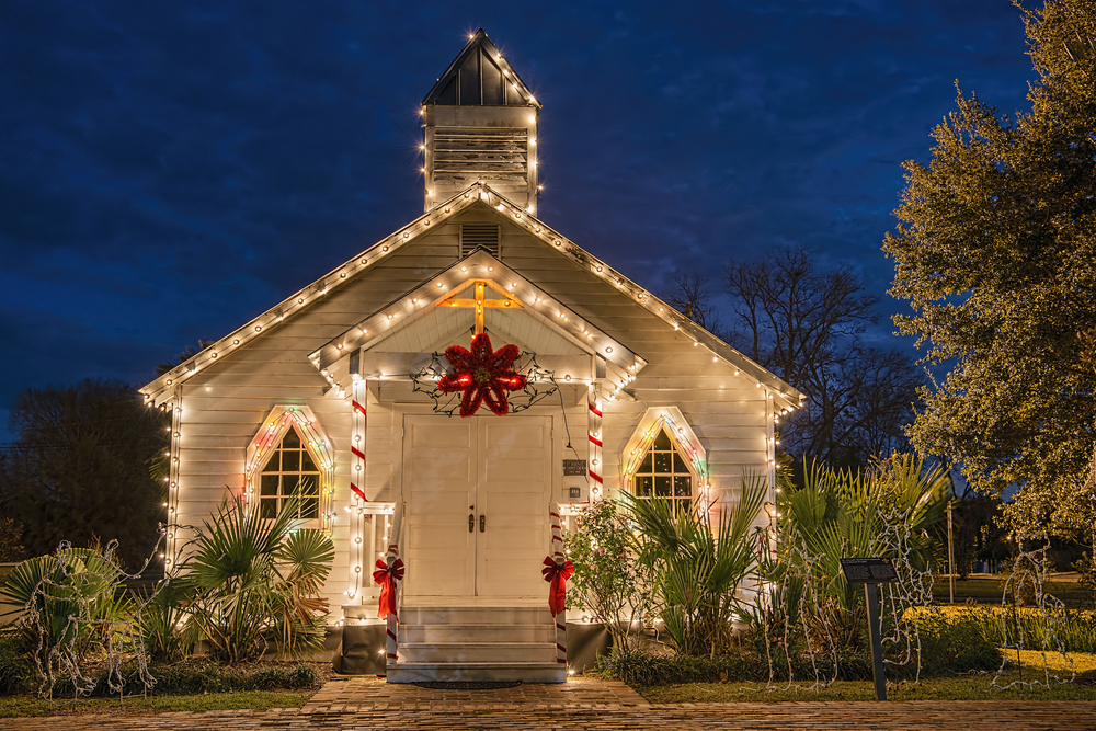 A simple old white church decorated with string lights, a red star, red ribbon, and a gold cross that lights up for celebrating Christmas in the south. In font of the church is palm trees.