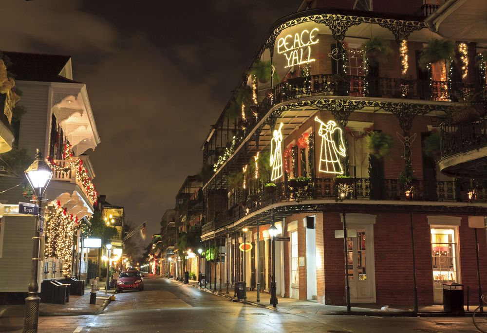 Buildings in the French Quarter decorated for Christmas. There are light angels, a sign that says 'Peace Yall', and greenery with string lights on the balcony railings.