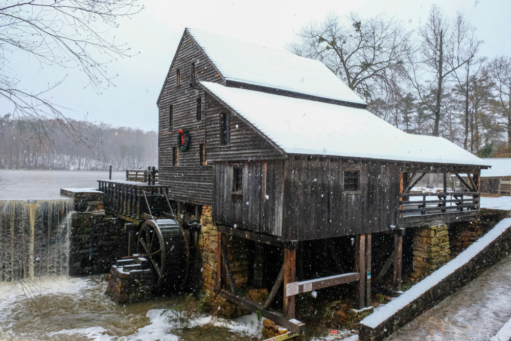 An old historic mill on the edge of a lake. It is snowing and there is snow on the ground. On the front of the old mill is a wreath with a red ribbon.