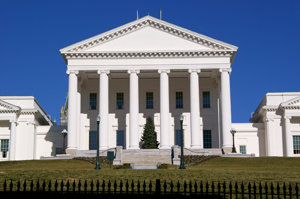The front of a large government building in Richmond, a great Christmas in the south destination. On the porch of the government building there is a large evergreen tree right in the middle.