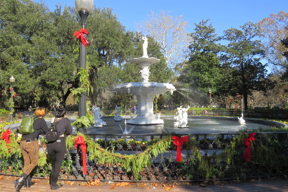Two people standing against a railing looking at a large fountain in Savannah Georgia, one of the best places to spend Christmas in the south. The railing and light poles are decorated in fresh greenery and red ribbons.