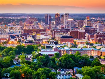 View overlooking the city of birmingham with green trees, city lights, and an orange sky.