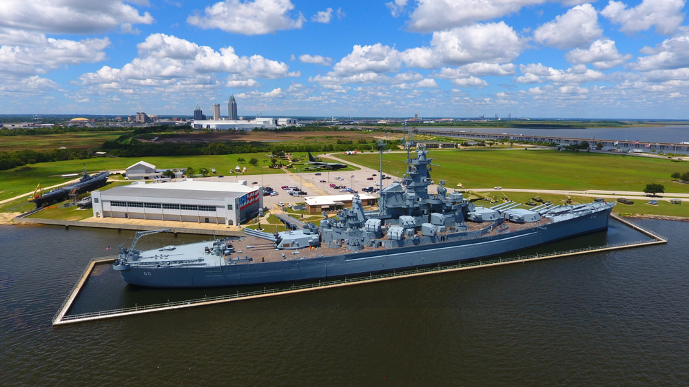 The battleship USS alabama with the city and the mobile bay in the background