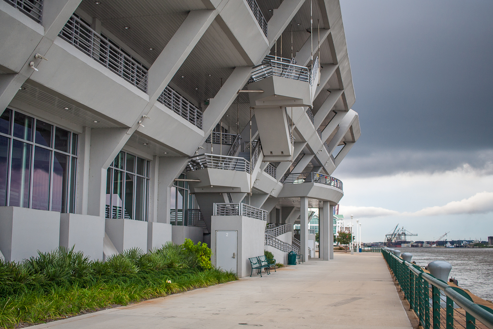 The Geometric grey building of the museum is located on Mobile Bay you can see port in the background