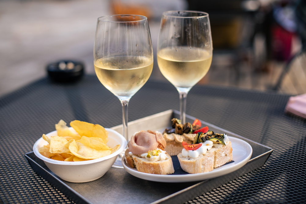 two white wine glasses with food on table