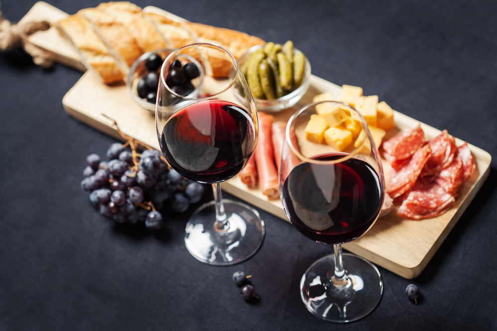 two glasses of red wine with a meat and cheese platter