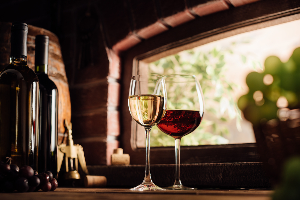a glass of red wine and a glass of white wine on a wooden table