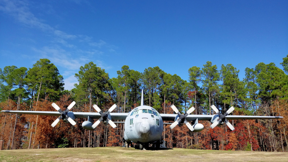 Photo of a military Airplane surrounded with tall foliage covered trees at 82nd Airborne Division War Memorial Museum