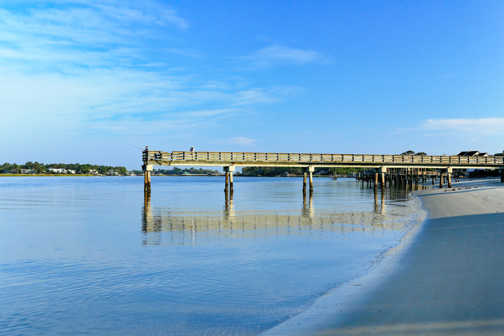 A fishing pier stretches into the water at Back River Beach, of the best river beaches in Georgia.