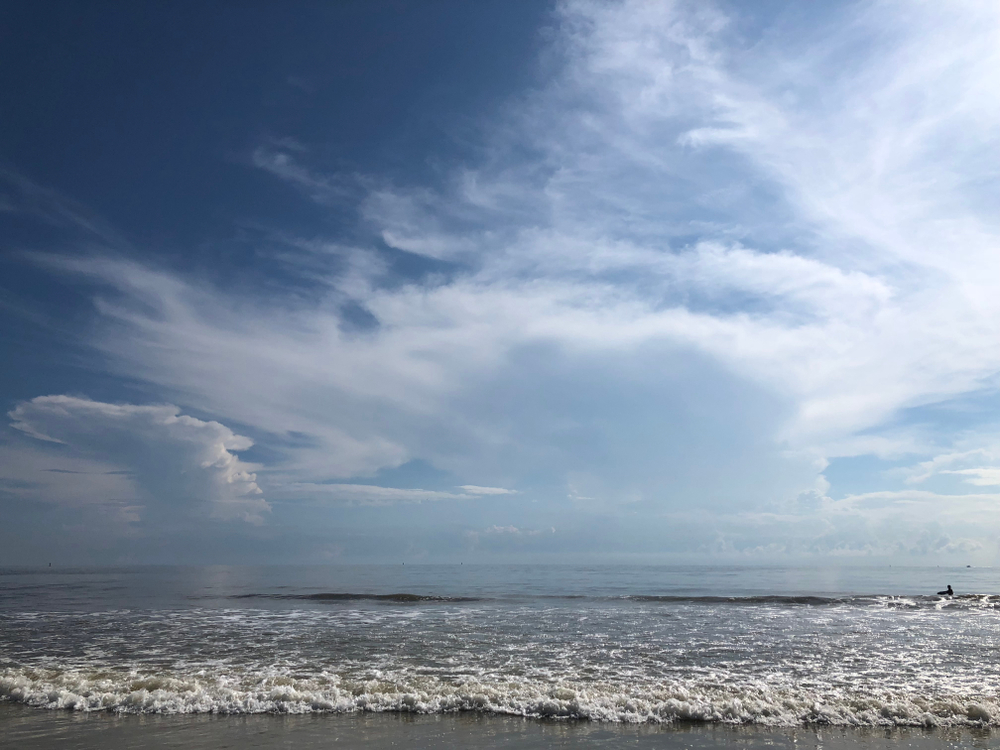 A cloud-filled sky over the waves hitting North Beach on Tybee Island, one of the best beaches in Georgia.
