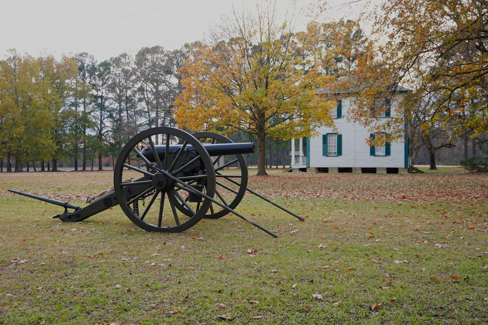 Photo of a cannon and historic home surrounded by tall trees at Bentonville Battlefield State Historic Site