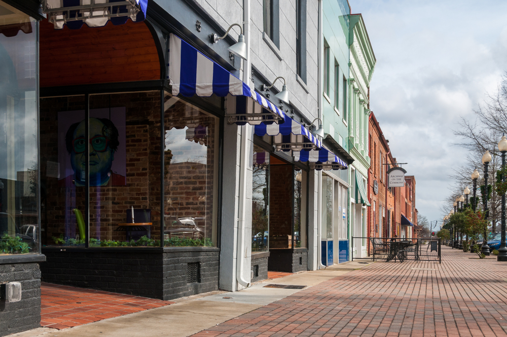 Photo of colorful buildings and a brick paved sidewalk in historic downtown Fayetteville.