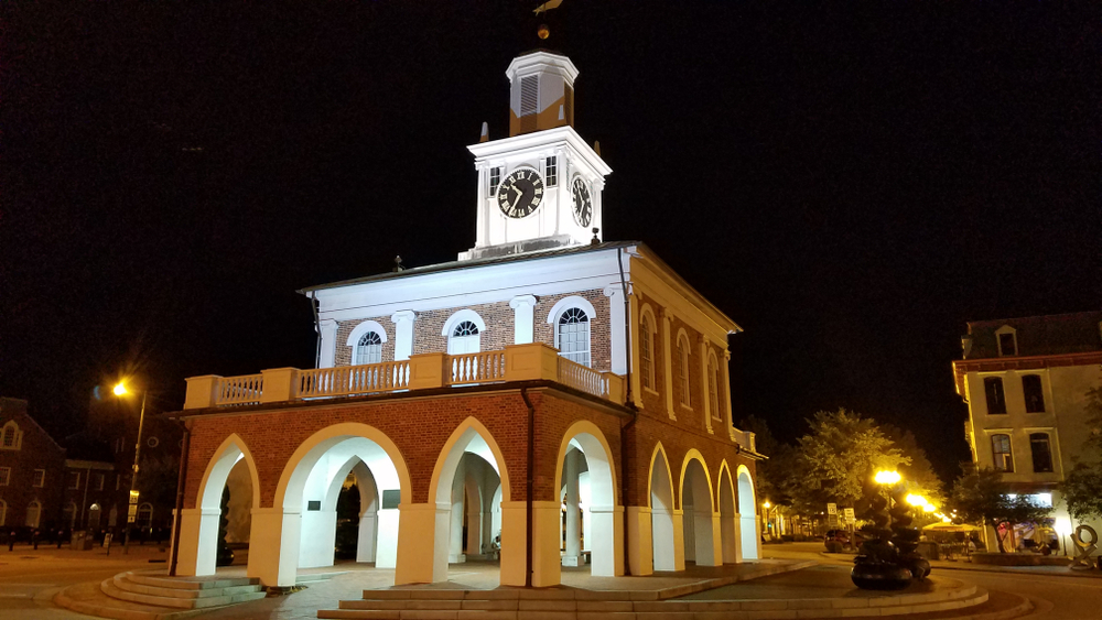 Photo of Market Hall, a red brick building topped with a clock tower, lit up at night.