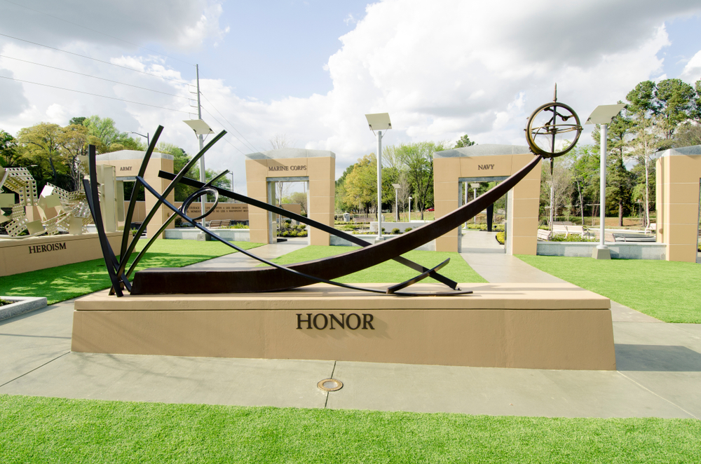 Photo of an abstract memorial sculpture that says honor, surrounded by other sculptures that say heroism, Army, Marine Corps, and Navy at North Carolina Veterans Park, one of the best things to do in Fayetteville North Carolina.