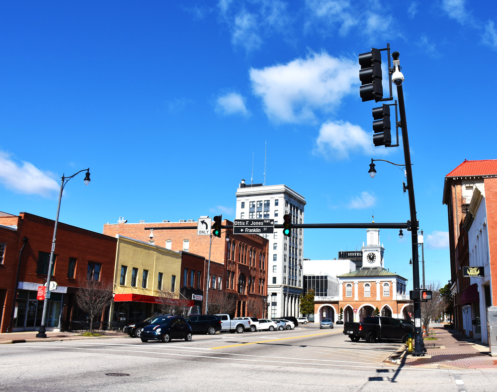 Photo of buildings and a stop light in downtown Fayetteville North Carolina with Market House at the end of the street.