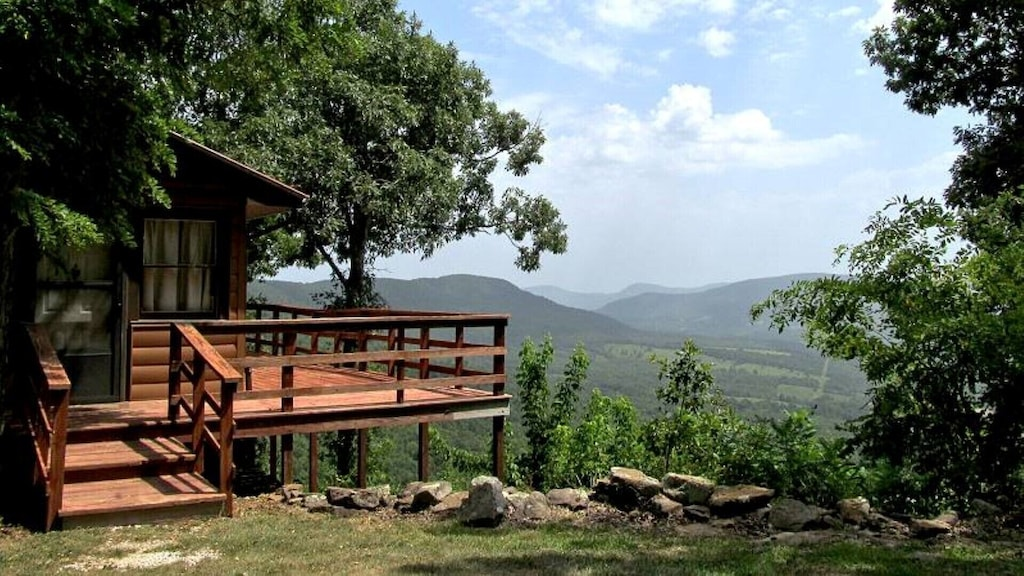 large porch overlooking mountains, trees around the cabin and porch
