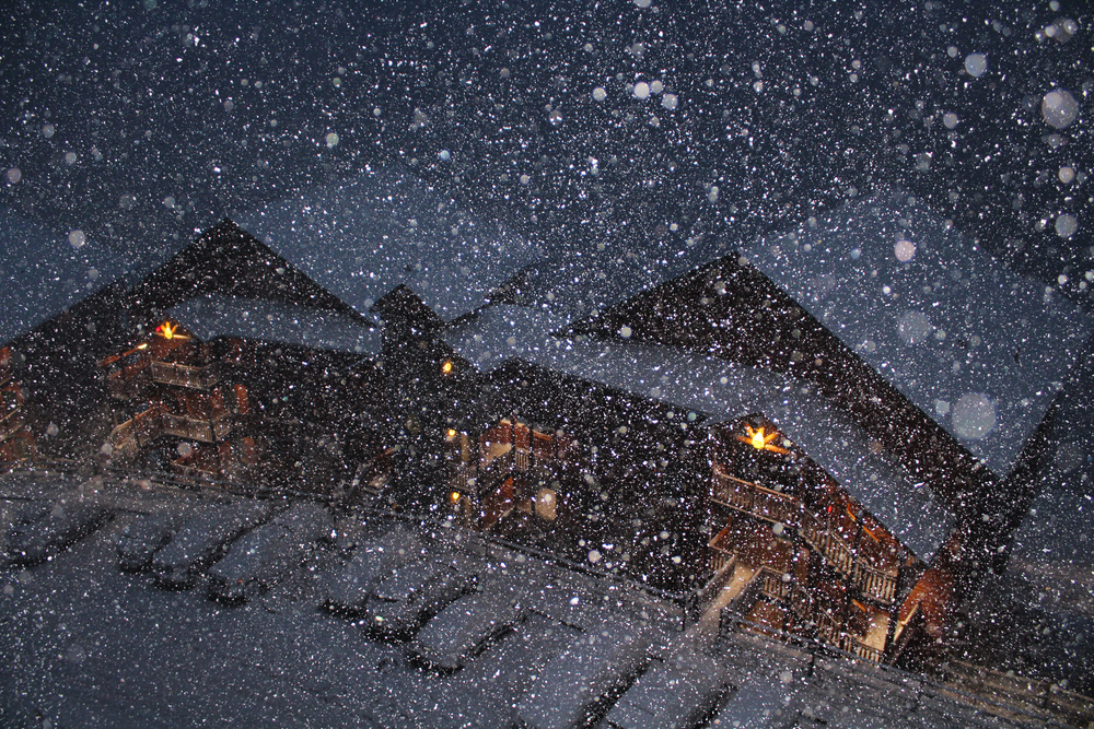 snow falling in front of wood buildings with snow covered roofs