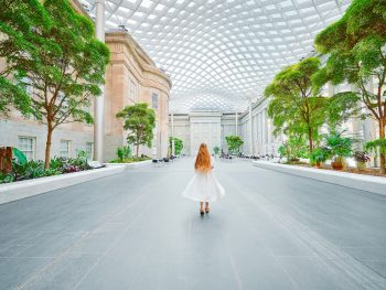 A woman in a white dress with long hair walking in the courtyard of the National Portrait Gallery, one of the best things to do in Washington DC. There are trees, shrubs, a wavy glass ceiling, and building facades.